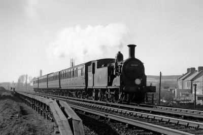 """LSWR Drummond M7 class 0-4-4T no. 30049 with pre-grouping stock photographed whilst in charge of a Horsham - Brighton service at Aldrington halt in February 1953. The two coacheS behind the engine are pure LBSCR but I'm not sure about the other two. Aldrington Halt was originally called Dyke Junction Halt but was renamed in 1932 and is still present today but without the 'Halt' in the name. 30049 was a Horsham engine when this shot was taken and would later move to Brighton in 1959 and then to Guildford in 1961 where withdrawal would take its toll in May 1962. Some interesting supporting notes from Chris Knowles-Thomas regarding the rolling stock: """"Yes, the first two coaches are a pull-push set of LBSCR origin - would appear to be set 650 or 651.  The rear two are another p-p set, this time of LSWR origin, one of sets 652-655.  The third coach is a 58ft trailer third created by rebuilding a LSWR 50ft compo on an SR 58ft underframe (Nos. 1-4) while the fourth is a reframed LSWR 46ft 6in driving brake compo converted from a LSWR 46ft 6in 'Emigrant' lavatory third (Nos. 6428-6431)."""""""