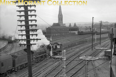 The magnificent steeple of Exeter's Anglican church of St Michael and All Angels in its entirety dominates the background to this shot taken from close to Central station as maunsell 'Z' class 0-8-0T no. 30955 pilots 'N' class 31842 in charge of a passenger train descending to St. David's station at river level. The image is brimming over with interest beyond that of a Southern double-header with those wagon turntables in the right foreground and the carriage sidings beyond the main line both centre and left of picture. The signal gantry in the foreground is a nice touch even if it partly obscure the 'Z' and I wonder if there was once another signal arm directly above the post. Chris Osment informs me that theis semaphore controlled the exit from the Up Sidings onto the Up Local (platform line). [Mike Morant collection]