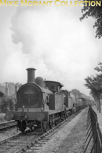 """Stirling ex-SER R1 0-6-0T No. 31107 and a cut down class compatriot double-head a goods train at sometime in 1958.  An interesting contribution from David Woodcock: """"Both locos are working very hard and I suspect that the location is where one might expect to find R1s in multiple heading a train - the Folkestone Harbour branch. The first wagon appears to be an (empty) oil tank wagon for ship's bunkerage and, perhaps surprisingly, there was still a thrice-weekly cargo service between Folkestone Harbour and Boulogne using TSS Whitstable (in her last year in 1958) and TSS Deal."""""""