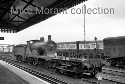 SECR Wainwright 'D' class 4-4-0, a Guildford engine, with a shunter's truck as its companion, stands at the edge of the carriage sidings at Clapham junction on 31/8/56.