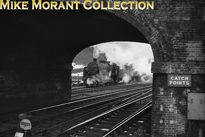 My type of picture. Clive Standen & Peter Smart have, between them, defined the location as Guildford looking south through the eastern brick arches of what was the mainly iron Farnham Road Bridge.  The photographer had positioned himself way beyond the end of platform 3 for this shot of Maunsell U class mogul No. 31611 perfectly framed as it pulls out of the sidings behind Guildford South signal box.. [Mike Morant collection]