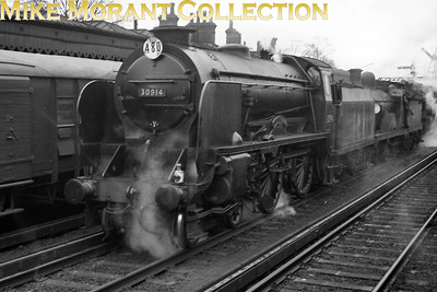 Maunsell Schools class 4-4-0 no. 30914 Eastbourne passes through Redhill station at the head of a multiple light engines movement. 30914 is in lined black livery with the first BR crest on its tender and the shed plate is 74B Ramsgate where it was based until 1959 but the second engine is a Wainwright 'D' class 4-4-0 which dates this shot to 1956 or earlier. [Mike Morant collection]