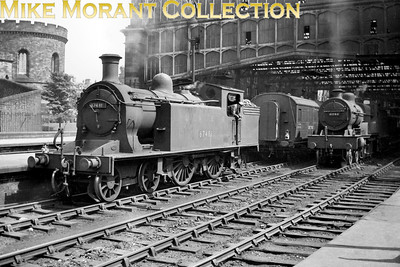 This period piece taken at the northern end of Carlisle Citadel station depicts NBR Reid C15 4-4-2T 67481 still proclaiming LNER ownership on the tank side but has had her new BR number applied in the form of the smokebox number plate. Lurking in the background is LMSR Fowler compound 4-4-0 41146. 67481 was withdrawn from 68E Carlisle (Canal) shed in February 1956 whilst 41146's life would be even shorter being withdrawn from 67A Corkerhill (Glasgow) as early as October 1954. The picture can be dated to the period July to October 1948.