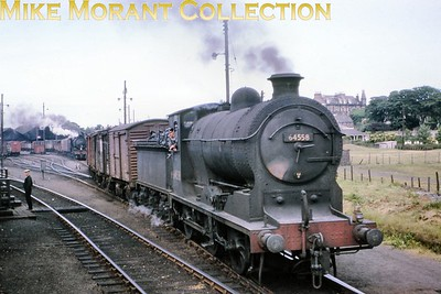 """Former NBR Reid designed J37 class 0-6-0 no. 64558 of 1918 vintage is depicted here in the goods yard at Montrose during July 1964. 64558 was allocated to 62B Dundee Tay Bridge when this picture was taken from the window of a passing train. Withdrawal at the same shed came in September 1965. John Duffy pinpoints the location with """"The distinctive building in the background with the dormer windows and the tower sits at the junction of High Street and Hume Street."""" [Mke Morant collection]"""
