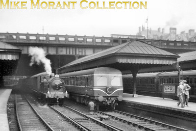 Former NBR Holmes designed J83 class 0-6-0T no. 68481 is shown here on station pilot duty alongside a moustachioed DMU at Edinburgh Waverley station in June 1957. Photo taken by Mike Morant