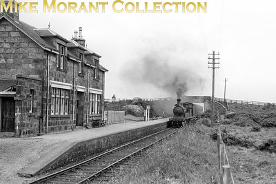 I couldn't resist bidding for this negative and obviously won it at auction. This is the former Great North of Scotland station at Mormond on the line from Fraserburgh to Maud Junction and is depicted here in BR days as Mormond Halt which had been implemented by the LNER in 1939. A pretty and pristine station building in my opinion but closure came in October 1965. the line was finally demolished in 1979. On 6/7/50 the train is entering Mormond Halt from the Fraserburgh direction, the previous stop was Lonmay, and is headed by GNSR Pickersgill designed D41 class 4-4-0 no. 62228 which had been built by Neilson's in December 1893. 62228 was a Kittybrewster allocated engine when this shot was taken which limits the date range for this shot to somewhere between September 1948 and August 1951 when it was transferred to Keith whence withdrawal came in February 1952. [G H Robin / Mike Morant collection]