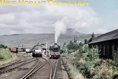 An unidentified Stanier Black '5' poses alongside the modified Coronation beaver tail observation car at Crianlarich (Upper) in September 1960. I was a passenger on the train with the observation car on the way to Fort William just for the experience of travelling on that wonderfully scenic line. [Slide taken by Mike Morant]