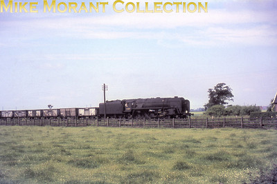 With no data on the slide mount other than the loco's number and an impossible date (it had been long withdrawn before that date) there's little one can write. This is BR Standard 9F 2-10-0 no. 92089 hauling some open wagons.