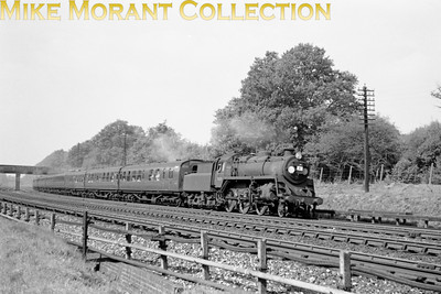 A summer Saturday in 1959 sees BR Standard 4MT 2-6-0 No. 76009 leaning to the curve at Brookwood whilst hauling an up express from Lymington Pier whilst the train is visibly packed with holiday makers returning from the delights of the Isle of Wight.