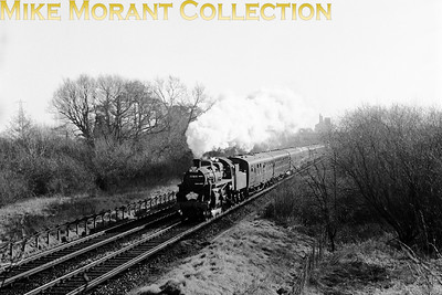 LCGB: The South Western Suburban Rail Tour 5/2/67 BR Standard 2MT 2-6-0 no. 77014 on the Staines to Windsor & Eton Riverside line, viewed from the embankment where the Staines branch crossed over. 77014 was the motive power for much of this tour and hauled it from Waterlook via East Putney to Chessington South and back to Wimbledon Park, Twickenham to Windsor & Eton Riverside and Surbiton to Hampton Court by which time it was too dark for lineside photography. 77014, something of a wanderling, would, just five months after this shot was taken, lay claim to being in charge of the very last timetabled steam hauled passenger train in the south of England. [Mike Morant collection]