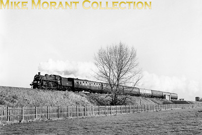 LCGB: The South Western Suburban Rail Tour 5/2/67 BR Standard 2MT 2-6-0 no. 77014 between Tolworth & Chessington North stations. 77014 was the motive power for much of this tour and hauled it from Waterlook via East Putney to Chessington South and back to Wimbledon Park, Twickenham to Windsor & Eton Riverside and Surbiton to Hampton Court by which time it was too dark for lineside photography. 77014, something of a wanderling, would, just five months after this shot was taken, lay claim to being in charge of the very last timetabled steam hauled passenger train in the south of England. [Mike Morant collection]