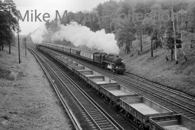 The Bournemouth Belle on the up slow line at St. John's Hill near Brookwood with, most unusually, careworn Standard 5MT 4-6-0 no. 73119 in charge. This shot was taken on Sunday April 25th, 1965 when all except this service were diverted via Guildford. The engineering train is in the charge of Maunsell 'N' class mogul no. 31858. Note, also, the Western liveried BG behind 73119's tender. [Mike Morant]