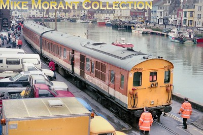 "This subject isn't my cup of tea but I bought the negative because the location is on the Weymouth Harbour Tramway. The unit is Railtrack Sandite/De-icing 3-car unit no. 930301 which was a conversion from a 205 class DMU. Does anyone know when this unit ran the length of the tramway in the second half of the 1990's? And the answer, a more interesting one that I could have hoped for, has been sent to me by Dennis Harlow to whom go my grateful thanks: ""I  was an operations manager on board this service which was in March 1999. The rear power car suffered a fractured cooling fan shaft and so the unit was left at Weymouth and was, I believe, towed back to Selhurst some time later"". [Mike Morant collection]"