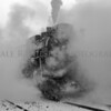 Pere Marquette Railway Steam Locomotive No.1225 enveloped by steam and snow back light by the sun peeking through the clouds. (B & W photo)