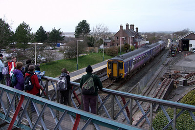 A group of onlookers watch 156479 head out of Ravenglass with the 1604 to Preston, 08/04/10.