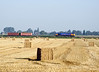 66721 passes a field of recently harvested grain (wheat or barley) and the straw bales awaiting pick up.