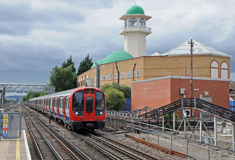 Sunday July 1st; at Willesden Green an Aldgate bound train of S stock speeds past the Central Mosque of Brent