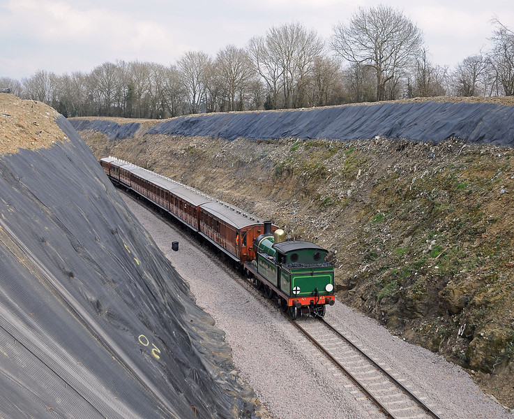The train returned at 12:00, here approaching Imberhorne Lane and passing through the remains of the waste tip. The leading bogie coaches are the ex-Metropolitan Ashburys set.