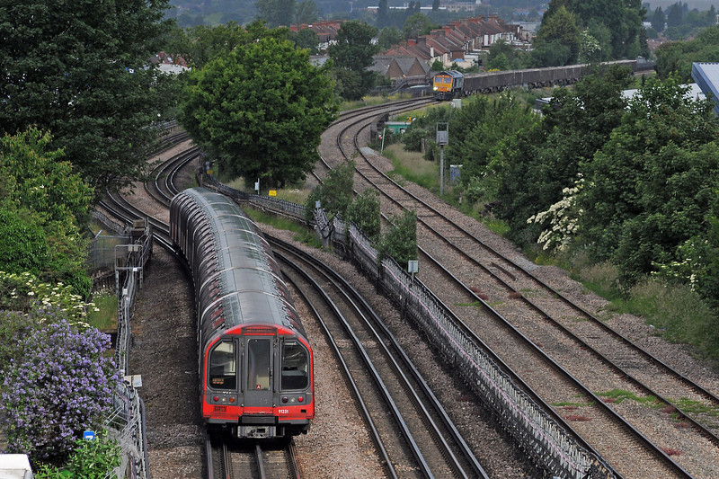 A West Ruislip bound train leaving as the 6V88 Northfleet to Paddington empty spoil train approaches from Greenford East Junction.