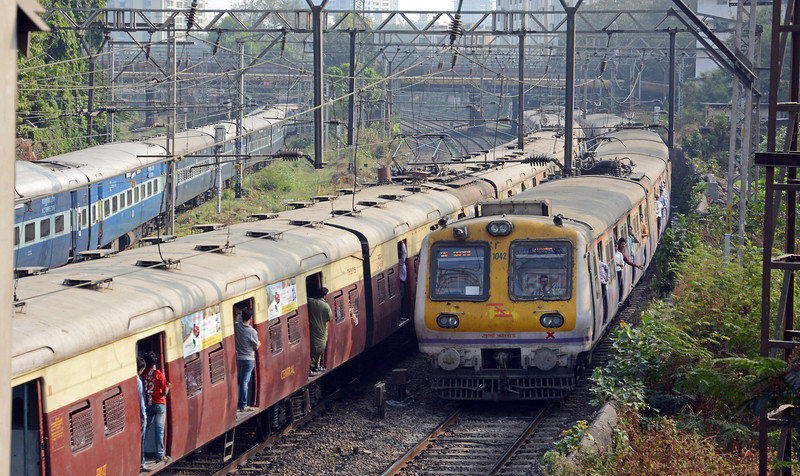 Just south of Byculla an outbound and inbound train pass each other, whilst on the left a long distance service enters the carriage servicing yard.