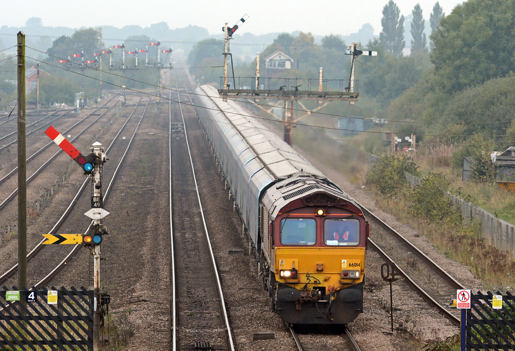 The departing tin rocket just missed 66014 on the 4R49 Drax to Immingham empty bio-mass hoppers. The signal is off for...
