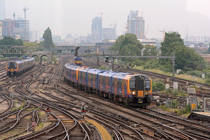A trio of 450s from the carriage sidings is about to enter the washer, whilst another pair on an Alton service draw up in platform 10. The London skyline is ringed with cranes, attesting to the phenomenal amount of construction going on.
