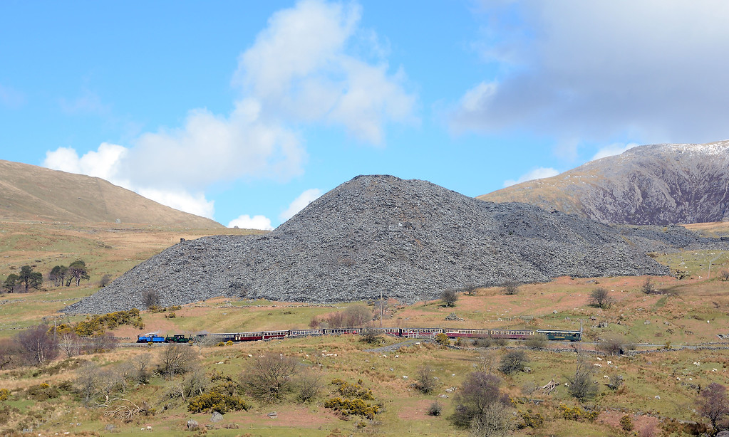 Slate quarry tailings tower over the Snowdonian as it descends towards Snowdon Ranger