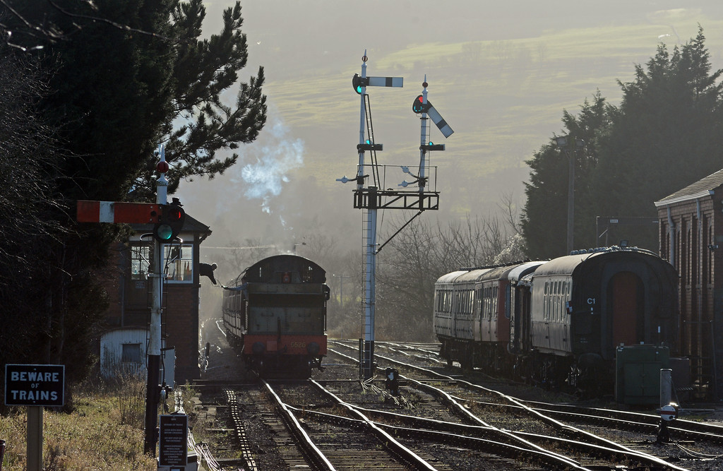 The train arrives, the fireman returning the token to the signalman.