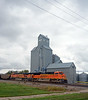 The helper power on the rear of the train passing the older grain elevator in town, 8464 is another SD70ACe.