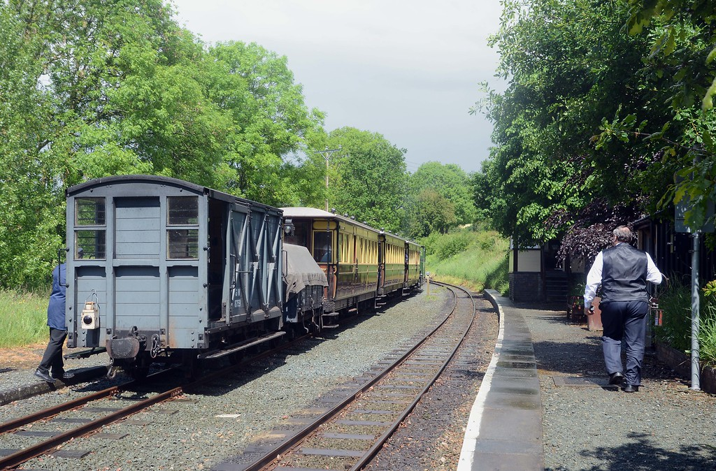 The signalman heads to the other end of the platform to collect the staff from the train from Welshpool.