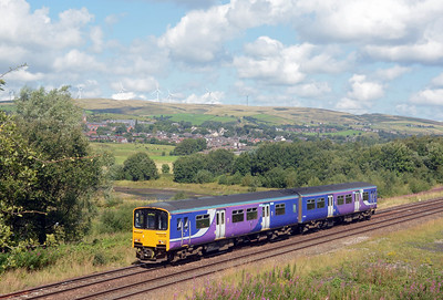 Wind turbines line the Pennine ridge behind the village of Wardle. 150 138 is bound for Leeds via Brighouse.
