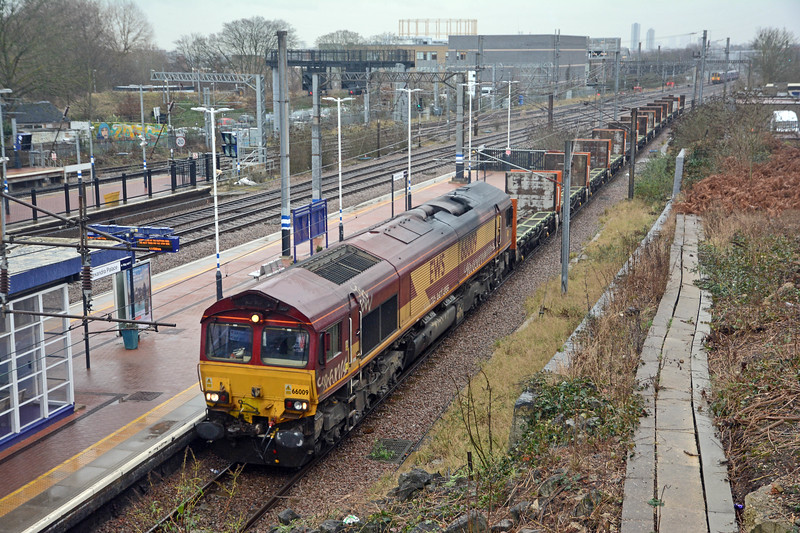 By late morning the rain, long promised, had started. 66009 on its way north with the empty Plasmor wagons on 4E25 Bow to Heck. In the background a Moorgate train is heading towards Hornsey, passing Heartlands High School