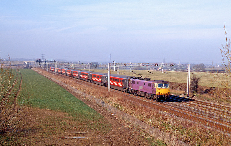 87002 in Porterbrook purple looks splendid as it hurtles south on a Euston bound train.