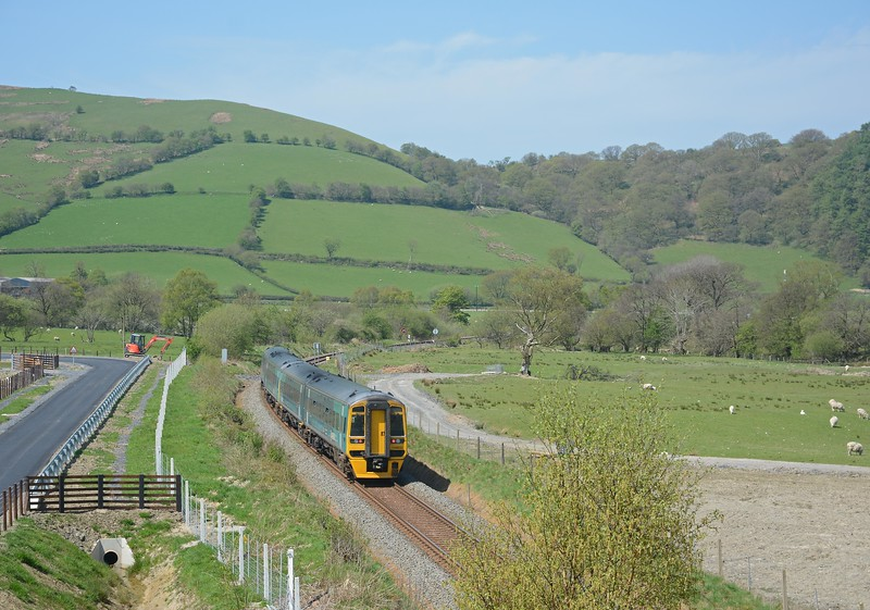 The passing loop is just beyond the speed restriction board. The 10:09 was running on time, unfortunately the 11:30 ex-Aberystwyth / 09:34 ex-Pwllheli wasn't! The latter was some 19 late off Tywyn. The bridge is very high, certainly with clearance for 25kV catenary, and the parapet, designed to deter rock throwing delinquents, requires steps. It all seems grossly over engineered