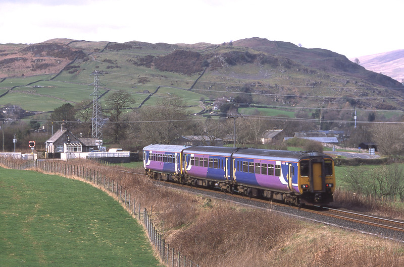 156440 brings up the rear of 153358 as they approach Staveley Barriers with the 14:22 Oxenholme - Windermere, 16/4/2018.