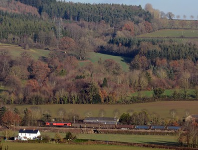 6M86 approaches Abergavenny's outer home, those are the ascending slopes of Ysgyryd Fach behind the train.
