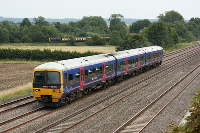 166214 passes Cholsey Manor Farm with 1257 Paddington - Oxford as the preserved branch line train departs Cholsey in the background 26/7/14