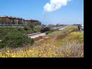From the archives, and an old Kodak DX6490 camera. Santa Fe 4-8-4 steam locomotive and excursion train perform an awesome photo run-by at Carlsbad Poinsettia on 6-1-08. The occasion was a steam special on a mainline that hadn't seen a steam engine since Santa Fe last ran this one and others like it in the 1950s. The line now sees Amtrak Pacific Surfliners, Coaster commuter trains, and light freight traffic.