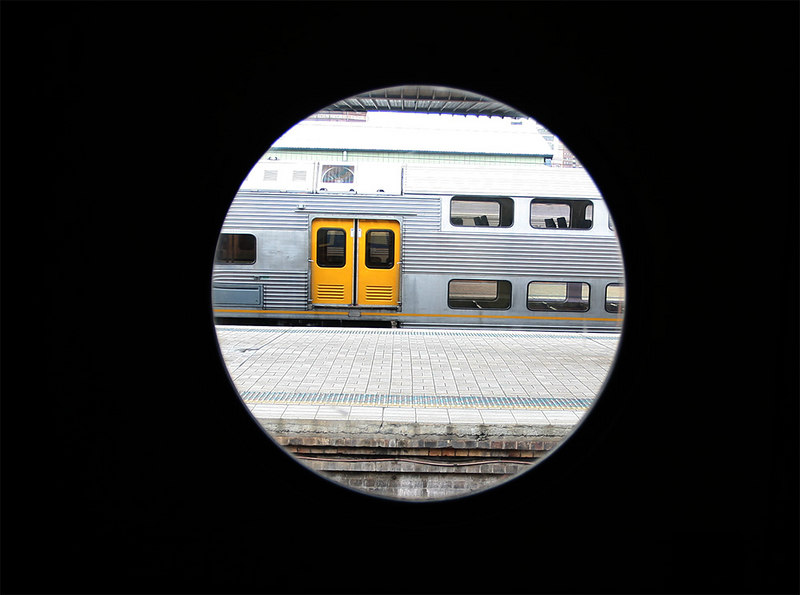 Through the upper door of the 3801 carriage looking at a modern stainless steel car at Central.