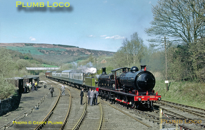 The NYMR Royal opening special train stands on the junction between the BR line from Middlesbrough to Whitby and the NYMR itself at Grosmont, prior to moving into the platform to pick up the train's passengers, including HRH The Duchess of Kent. The train is double-headed by immaculate P3 class 0-6-0 (LNER & BR class J27) No. 2392 and LH&JCR 0-6-2T No. 29. It was originally intended that this train would start from Whitby, but a national rail strike that day put paid to that idea! Note the rusty rails of the main line in the foreground left, though the double track from here to Whitby was in the process of being singled at the time, the far left track already out of use and severed. Tuesday 1st May 1973, a beautiful Spring day. Slide No. 11034.