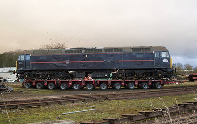 A side view of 47799 on the trailer on 22ndf December, with a flock of birds wheeliong about in the background.