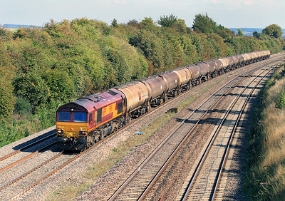A late running 6E55 13.35 Theale to Lindsey empty tanks heads through Moreton Cutting with 66199 in charge. 02/09/2011