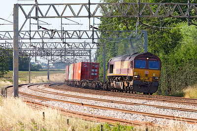 A very grubby 66134 powers round the curve approaching Heamies Farm on the Up Fast in charge of 4L56 13.17 Trafford Park Euro Terminal to London Gateway Intermodal service. Tuesday 19th July 2016.