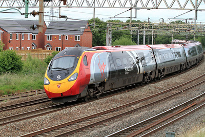 390004 in Alstom Pendolino vinyls forming the 13.40 Euston to Manchester rounds Queensville Curve at Stafford. 24/06/2011.