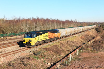 70802 heads the 6C36 12.20 Westbury to Aberthaw Cement Works empty PCA's past Church Road, Undy. Friday 20th January 2017.