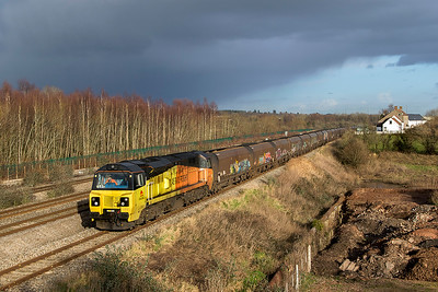 Under threatening skies 70809 passes Undy with 6B22 14.29 Avonmouth Coal Silo to Aberthaw Power Station loaded hoppers. Thursday 25th January 2018.