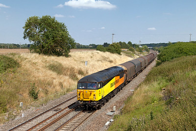 56113 passes Steppingstone Lane, Bourton with 6V62 11.22 Tilbury Riverside to Llanwern empty steel carriers. Wednesday 30th July 2014.