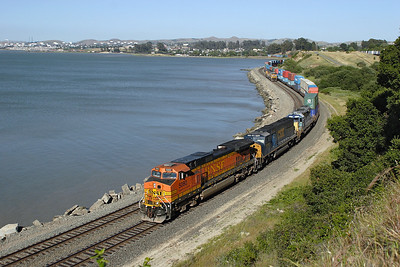 BNSF 5080 (C44-9W), CSX 8783 (SD60M) & CSX 8026 (SD40-2) wind their doublestack train around San Pablo Bay at Pinole and have just passed UP 4348 & UP 4408 (both SD70M's) in the process of running round a work train. In the top right background can be seen a train of intermodal stock on the adjacent BNSF line. Wednesday 5th May 2007.