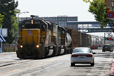 UP 3270 (SD40-2R) & UP 2831 (SD40T-2) Ex SP 6863 head a transfer freight through Jack London Square station and into the street running area and mixing with the cars. 26/04/2007.