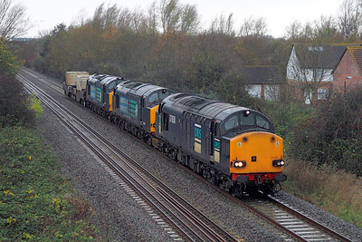 More loco's than wagons! 37038 & 37606 with failed 37667 dead in train with FNA's 550018 & 550029 as the 6M67 Bridgwater to Crewe, head through the rain and winds at Locking Castle on the Weston-super-Mare avoiding line. Thursday 22nd November 2012.